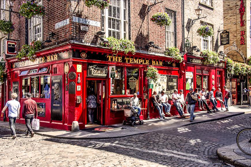 La gente se relaja y toma una copa frente a la famosa cerveza irlandesa The Temple Bar en el corazón de la capital irlandesa