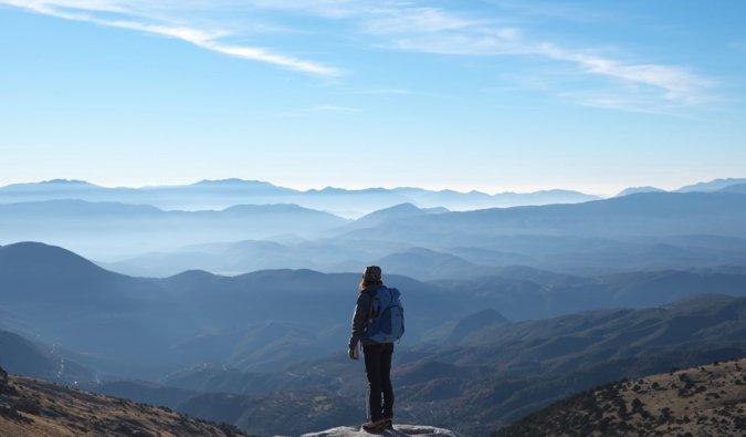 Viajero femenino solitario de pie en la montaña
