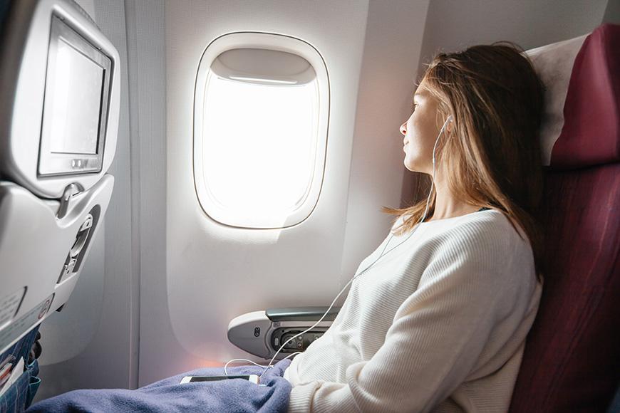 Un adolescente mirando la ventana de un avión mientras está en vuelo.