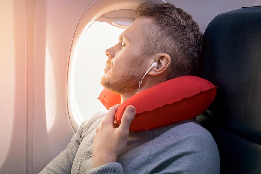 Un avión de pasajeros masculino escucha música y disfruta durmiendo en una silla