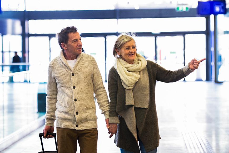 una pareja mayor paseando por el aeropuerto señalando una bufanda y suéteres